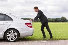 Full length side view of young businessman pushing broken down car at countryside Stock Photography