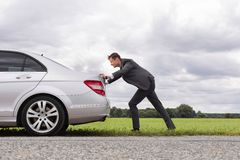 Full length side view of young businessman pushing broken down car on road Royalty Free Stock Photography