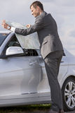 Full length side view of young businessman reading map by car at countryside Royalty Free Stock Images