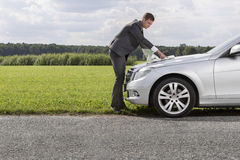 Full length side view of young businessman reading map on car hood at countryside Royalty Free Stock Photos