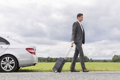 Full length side view of young businessman with suitcase leaving broken down car at countryside Stock Photos