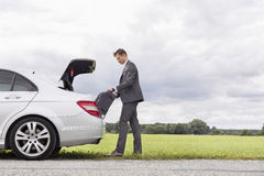 Full length side view of young businessman unloading luggage from broken down car at countryside Royalty Free Stock Photo