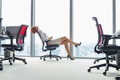 Full length side view of young businesswoman leaning back in chair at office Stock Photography