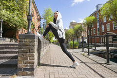 Full length side view of young fit woman stretching Royalty Free Stock Image