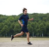 Full length side view of a young man running Stock Images