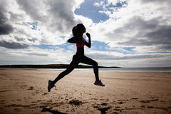 Full length of silhouette healthy woman jogging on beach. Full length of a silhouette healthy young woman jogging on shore at beach stock images
