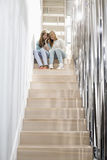 Full-length of sisters listening to music on stairway Stock Images