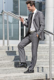 Full length of smiling businessman text messaging through cell phone while standing on steps outside office Royalty Free Stock Image
