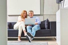 Full-length of smiling couple using laptop on sofa Stock Image