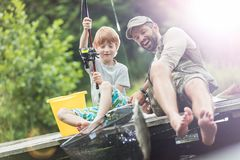 Full length of smiling father and son catching fish in butterfly fishing net royalty free stock images