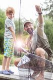 Full length of smiling father and son fishing on pier royalty free stock image
