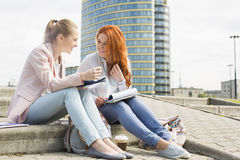 Full length of smiling female college students studying on steps against building Stock Photos