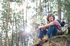 Full length of smiling male hiker looking away while sitting on cliff in forest Stock Photos