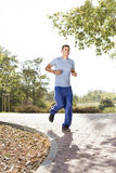 Full length of smiling man listening music while jogging in park Royalty Free Stock Photography