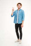 Full length of smiling man standing and showing peace sign Stock Image