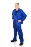 Full length smiling repairman with hands on hips Royalty Free Stock Image