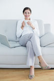Full length of a smiling well dressed woman with laptop and coffee cup on sofa Royalty Free Stock Images