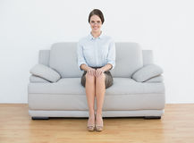 Full length of a smiling well dressed woman sitting on sofa Stock Photography
