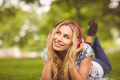 Full length of smiling woman listening to music at park Royalty Free Stock Photography