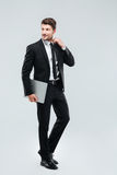 Full length of smiling young businesman with laptop. Over white background Stock Photography