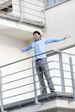 Full length of smiling young businessman standing arms outstretched at hotel balcony Stock Photos