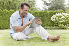 Full length of smiling young man using digital tablet in park Royalty Free Stock Photos
