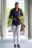 Full length smiling young man walking in city with mobile phone and bag. Full length portrait of smiling young man walking in city with mobile phone and bag Royalty Free Stock Photo