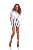 Full length of smiling young slim tanned female in denim shorts Royalty Free Stock Photography