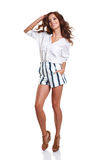 Full length of smiling young slim tanned female in denim shorts Royalty Free Stock Image