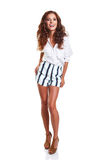 Full length of smiling young slim tanned female in denim shorts Stock Images