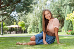 Full length of smiling young woman looking away while relaxing in park Stock Photo