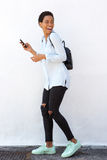 Full length smiling young woman walking with cellphone and bag. Full length side portrait of smiling young woman walking with cellphone and bag Royalty Free Stock Photo