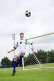Full length of soccer player playing with ball. On field against sky Royalty Free Stock Photo