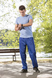 Full length of sporty man checking time on path in park Royalty Free Stock Photo