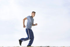 Full length of sporty man jogging against sky Royalty Free Stock Photo