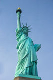 Full length Statue of Liberty against blue sky Stock Image