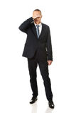 Full length stressed businessman covering his face Stock Photography