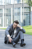 Full length of stressed businessman sitting on path outside office Royalty Free Stock Photo