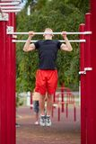 Young strong man does pull-ups on a horizontal bar on a sports ground in the summer in the city. Full-length of strong athlete doing pull-up on horizontal bar Stock Photos