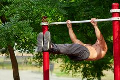 Young strong man does pull-ups on a horizontal bar on a sports ground in the summer in the city. stock images