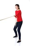Full length strong woman puling rope Stock Images