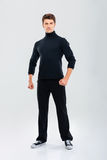 Full length of strong young man in black clothes standing Royalty Free Stock Photos