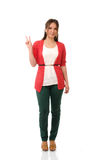 Full length studio portrait of a young beautiful woman showing peace sign Stock Images