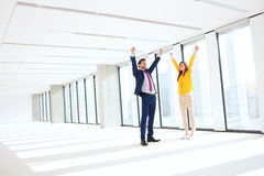 Full length of successful businessman and businesswoman with hands raised in empty office Royalty Free Stock Photography
