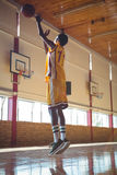 Full length of teenage boy playing basketball. In court Royalty Free Stock Image