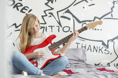Full-length of teenage girl playing guitar in bedroom Stock Images