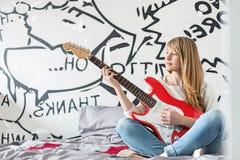 Full-length of teenage girl playing guitar in bedroom Stock Image