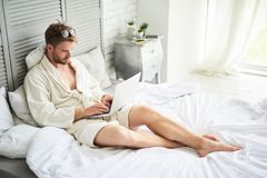 Busy male working on laptop in morning. Full length of tense young man lying on bed in bathrobe and holding computer. He is looking on screen with concentration Royalty Free Stock Photo