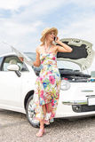 Full-length of tensed woman with map using cell phone by broken down car on road Royalty Free Stock Photos