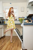 Full length of a terrified young woman looking at open oven Royalty Free Stock Photo